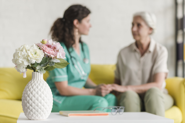 flower vase front nurse senior female patient sitting sofa 23 2147861481